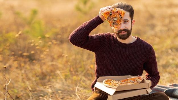 Hombre mostrando una rebanada de pizza con espacio de copia Foto gratis
