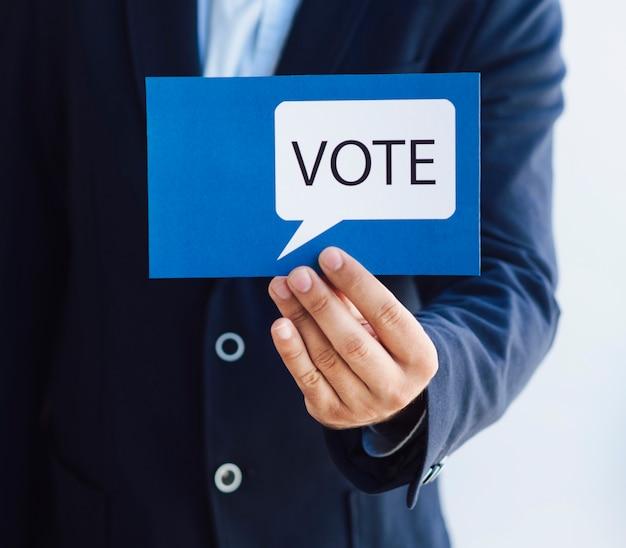 Hombre mostrando una tarjeta de votación con un bocadillo Foto gratis