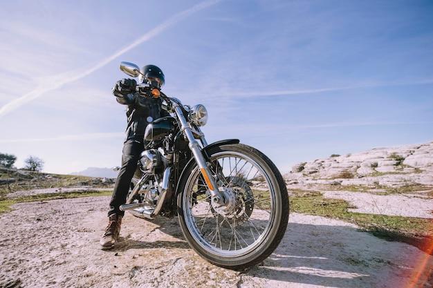 Hombre con moto en roca Foto gratis