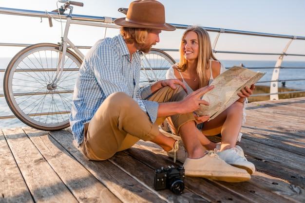 Hombre y mujer con cabello rubio estilo boho hipster moda divirtiéndose juntos, mirando en el mapa turismo Foto gratis