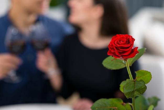 Hombre y mujer con una cena romántica de san valentín con rosa enfocada Foto gratis