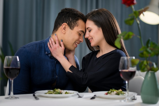 Hombre y mujer cenando en casa en san valentín Foto gratis