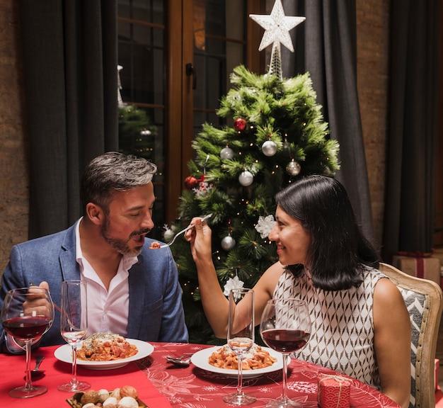 Hombre y mujer cenando en navidad Foto gratis