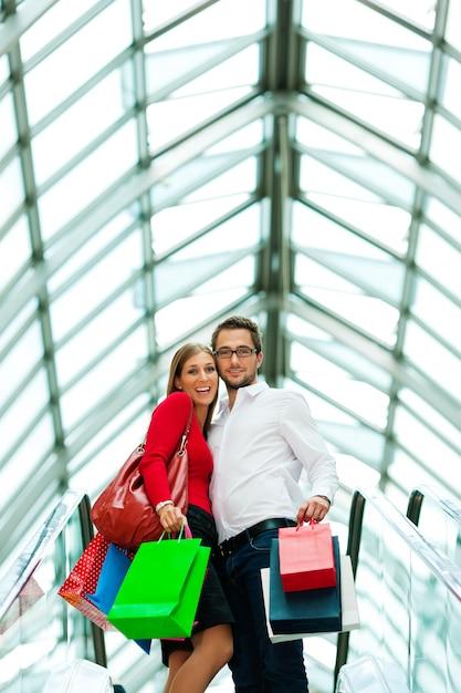 Hombre y mujer en centro comercial con bolsas Foto Premium