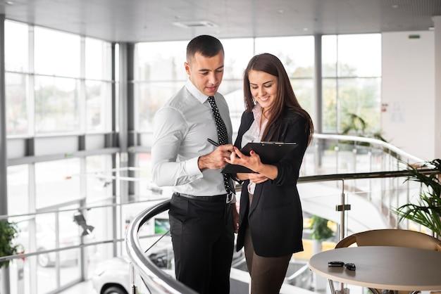 Hombre y mujer cerrando trato en concesionario Foto gratis