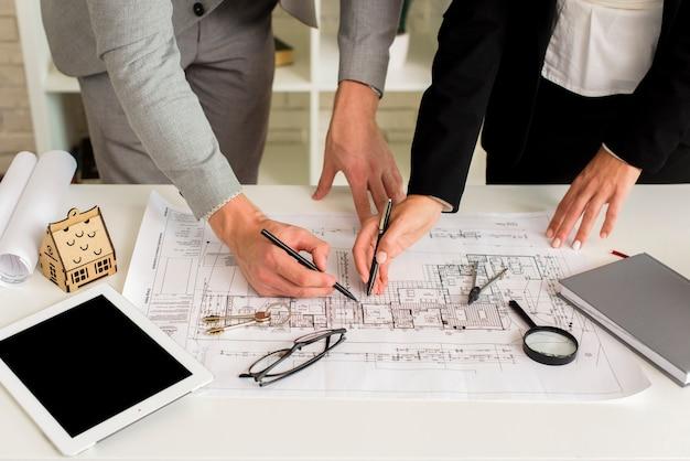 Hombre y mujer dibujando una maqueta de plan de casa Foto gratis