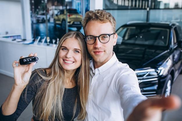Hombre y mujer eligiendo un automóvil en una sala de exposición de automóviles Foto gratis