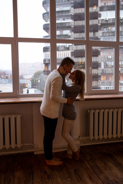 Hombre y mujer enamorados se abrazan de pie cerca de la ventana en casa Foto Premium