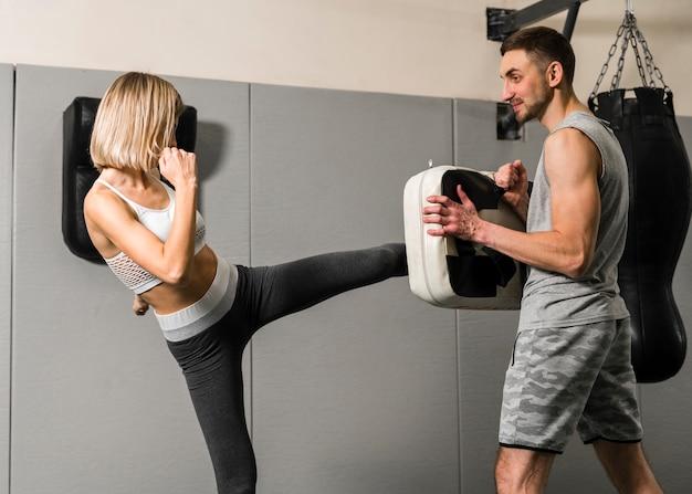 Hombre y mujer entrenando en el gimnasio Foto gratis