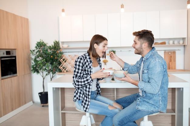 Hombre y mujer joven feliz en la cocina, desayunando, pareja juntos en la mañana, sonriendo Foto gratis