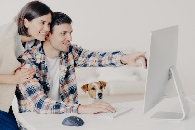 El hombre y la mujer joven feliz positiva trabajan remotamente en la computadora, pasan tiempo juntos, indican en el monitor, hacen reservas en línea, buscan información sobre hoteles, hacen planes para futuros viajes Foto Premium