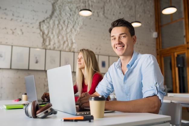 Hombre y mujer joven moderno que trabaja en la computadora portátil en la sala de oficina de coworking de espacio abierto Foto gratis