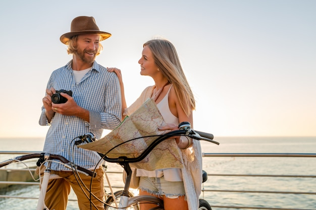 Hombre y mujer joven viajando en bicicletas con mapa Foto gratis