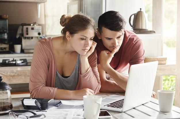 Hombre y mujer jóvenes trabajando juntos en una computadora portátil, pagando facturas de servicios públicos a través de internet o usando la calculadora de hipotecas en línea para ahorrar dinero en préstamos hipotecarios, mirando la pantalla con expresión seria y concentrada Foto gratis