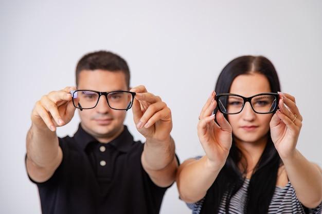 Hombre y mujer muestran anteojos modernos con bordes negros Foto Premium