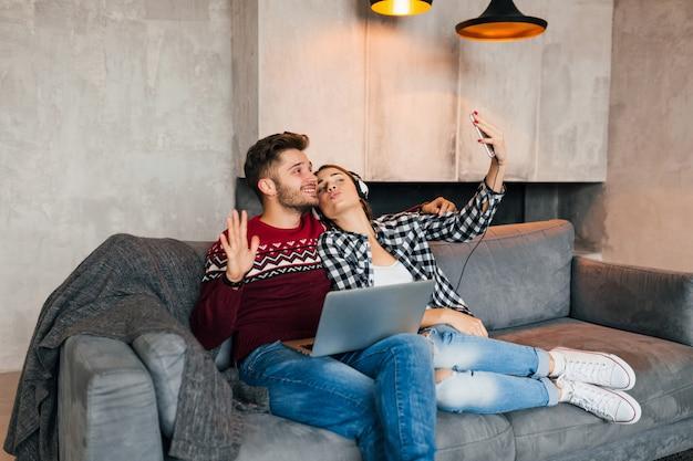 Hombre y mujer sonrientes jóvenes sentados en casa en invierno, trabajando en la computadora portátil, sosteniendo el teléfono inteligente, escuchando auriculares, pareja en el ocio pasando tiempo en línea, autónomo, citas Foto gratis