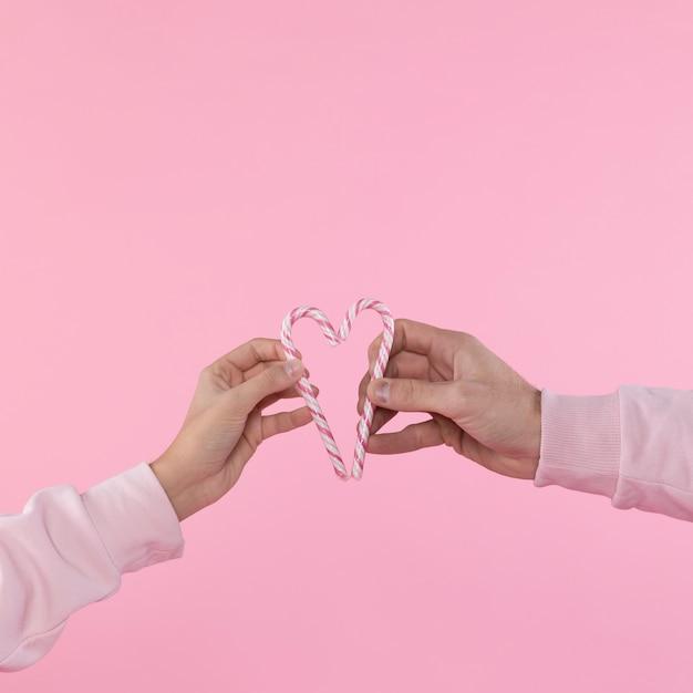 Hombre y mujer sosteniendo bastones de caramelo en forma de corazón Foto gratis
