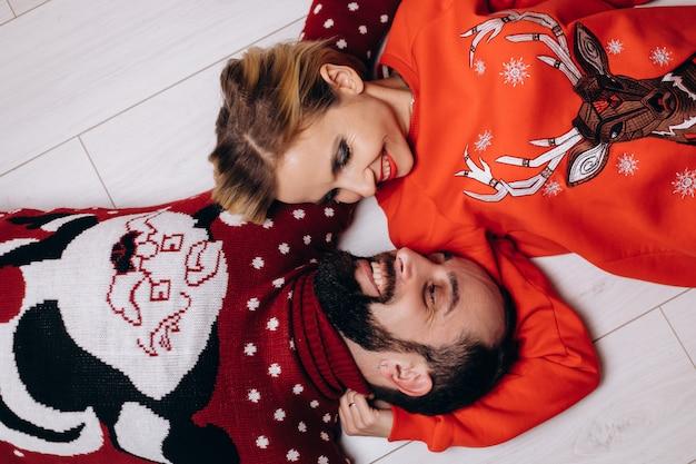 Hombre y mujer en suéteres de navidad se abrazan tiernamente mentirosos Foto gratis