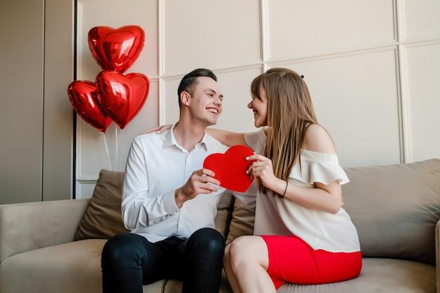Hombre y mujer con tarjeta de san valentín en forma de corazón rojo y globos en casa en el sofá Foto Premium