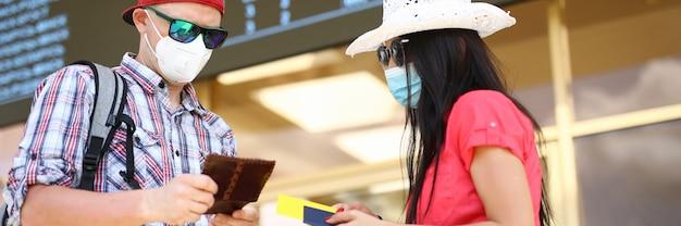 Hombre y mujer tienen pasaporte con retrato de billete de avión. viaje después del concepto covid-19 Foto Premium