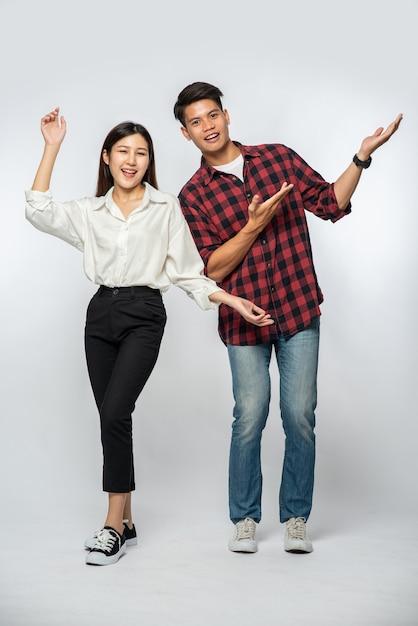 El hombre y la mujer vestían camisas y extendían felizmente sus manos hacia un lado Foto gratis