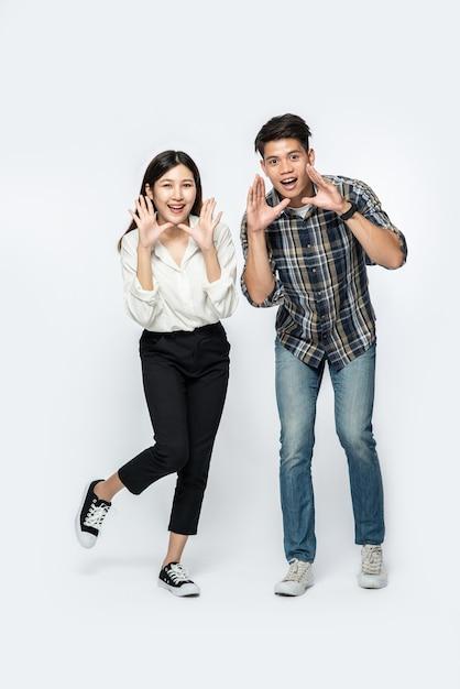 Hombre y mujer vistiendo camisetas y haciendo manos gritando felicitaciones Foto gratis