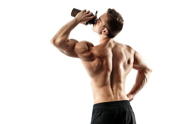 Hombre musculoso con bebida de proteína en agitador sobre fondo blanco. Foto Premium