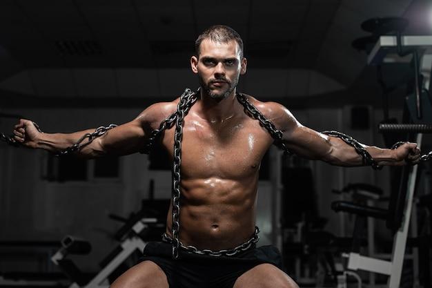 Hombre musculoso esclavo encadenado en gimnasio, el prisionero. Foto Premium