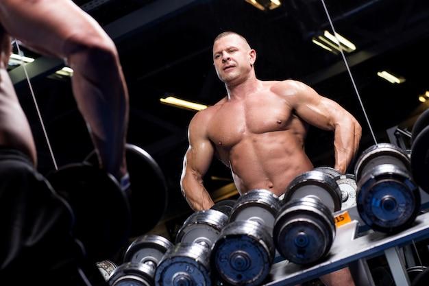 Hombre musculoso en un gimnasio Foto gratis