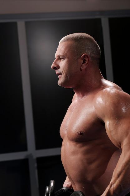 Hombre musculoso guapo en un gimnasio Foto gratis