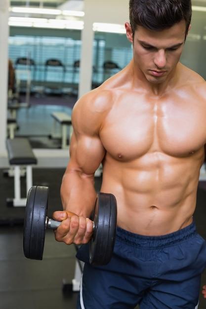 hombre musculoso haciendo ejercicio con pesas en el gimnasio