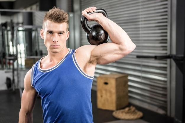 Hombre musculoso levantando pesas pesadas en el gimnasio de crossfit Foto Premium