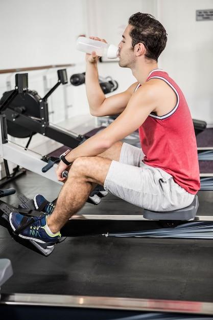 Hombre musculoso en la máquina de remo de agua potable en el gimnasio Foto Premium