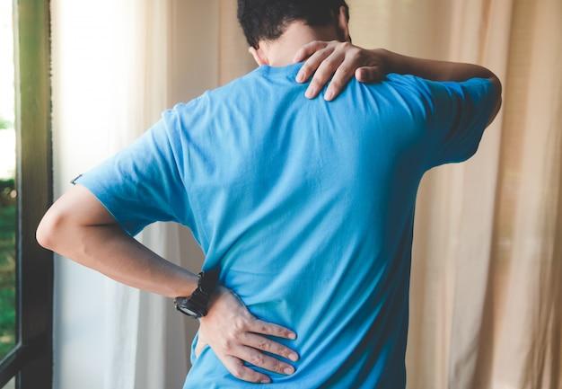 Hombre musculoso que sufre de dolor de espalda y cuello. problemas incorrectos de postura sentada espasmos musculares, reumatismo. alivio del dolor, concepto quiropráctico. lesiones por ejercicio deportivo Foto Premium