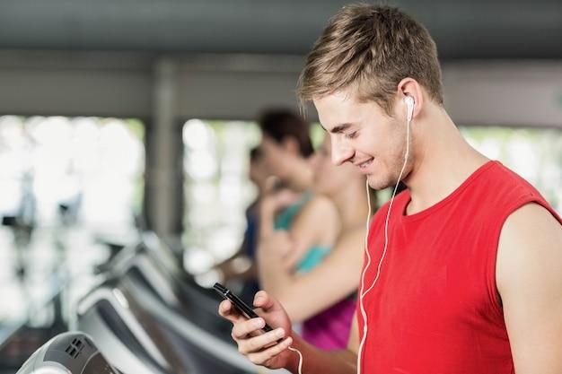 Hombre musculoso sonriente en la cinta rodante escuchando música en el gimnasio Foto Premium