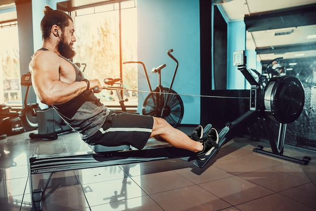 Hombre musculoso usando la máquina de remo en el gimnasio Foto Premium