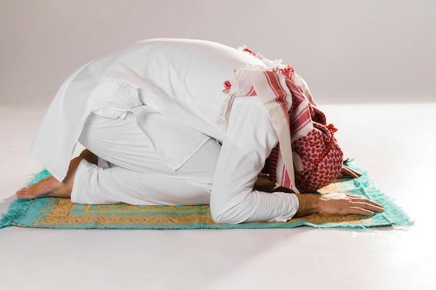 Hombre musulmán arco en reverencia vista frontal Foto gratis