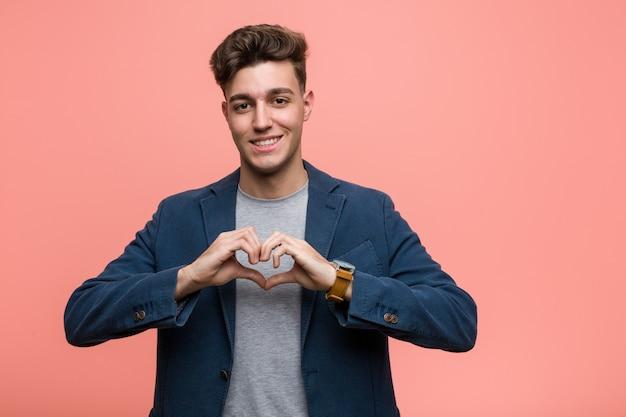 Hombre natural de negocios joven sonriendo y mostrando una forma de corazón con él las manos. Foto Premium