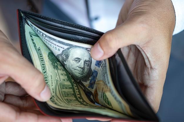 Hombre de negocios abrir billetera para ver billetes de dólar Foto Premium