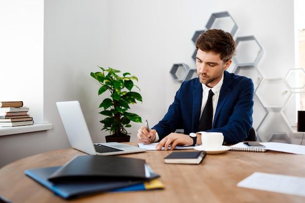 Hombre de negocios acertado joven que se sienta en el lugar de trabajo, fondo de la oficina. Foto gratis
