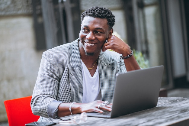 Hombre de negocios afroamericano usando laptop en un café Foto gratis