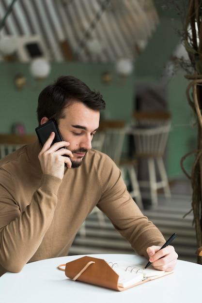 Hombre de negocios con agenda hablando por teléfono Foto gratis