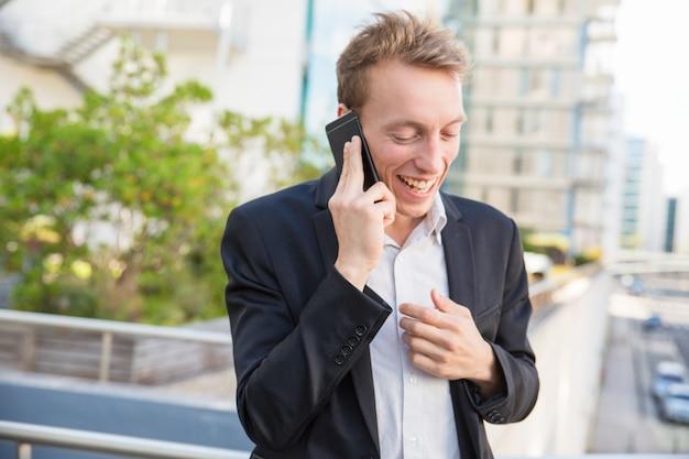 Hombre de negocios alegre emocionado chateando por teléfono Foto gratis