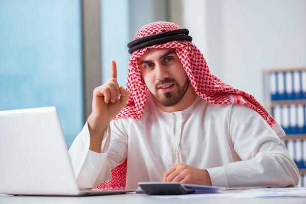 Hombre de negocios árabe que trabaja en la computadora portátil Foto Premium