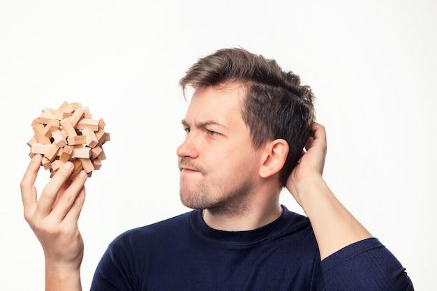 Hombre de negocios atractivo de 25 años mirando confundido en rompecabezas de madera. Foto gratis
