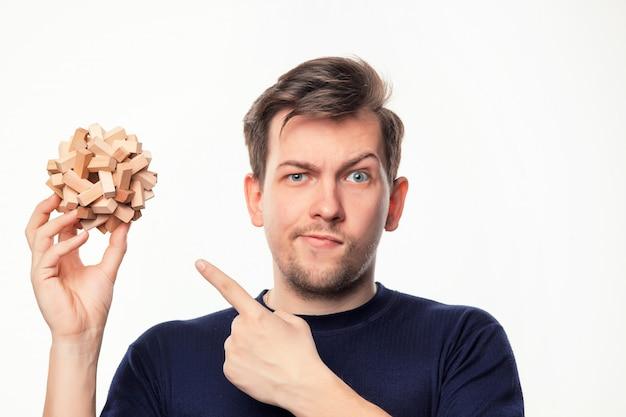 Hombre de negocios atractivo de 25 años que parece confundido con rompecabezas de madera. Foto gratis