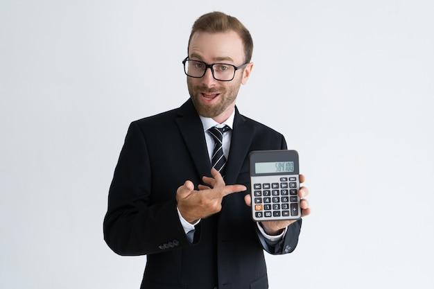 Hombre de negocios barbudo emprendedor que señala en la calculadora Foto gratis
