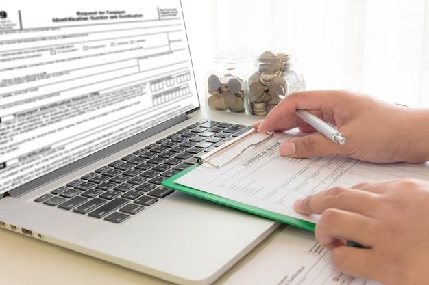 El hombre de negocios calcula cuentas en lugar de trabajo con el ordenador portátil en la oficina. Foto Premium
