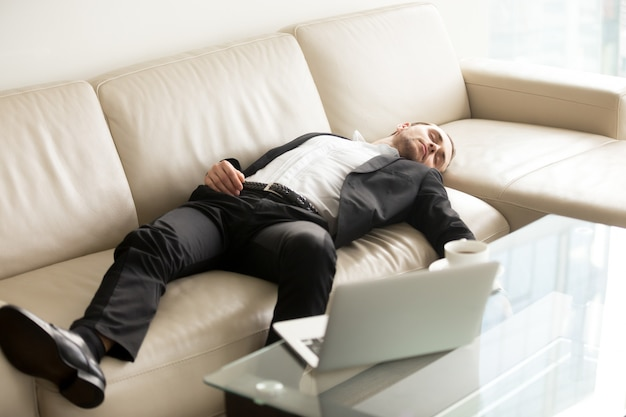 Hombre de negocios cansado que duerme en el sofá en oficina Foto gratis