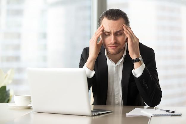 Hombre de negocios cansado que sufre de dolor de cabeza Foto gratis